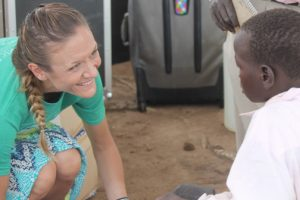 Amy Compston fits a shoe on the foot of a child during the Amy For Africa / Samaritan's Feet shoe distribution last week in Uganda. MARK MAYNARD / The Independent